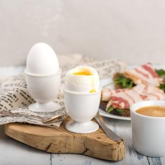 ゆで卵2個、殻付き、卵黄一滴、白い卵スタンド、木の板、テキスタイルナプキン、皿にベーコンを添えたトースト、一杯のコーヒー、明るい灰色の背景