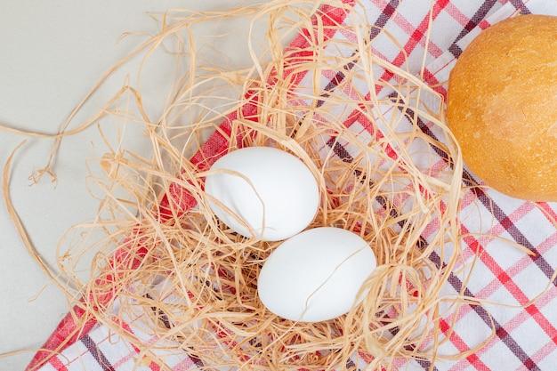 テーブルクロスの上に焼きたてのパンと2つのゆでた有機卵。
