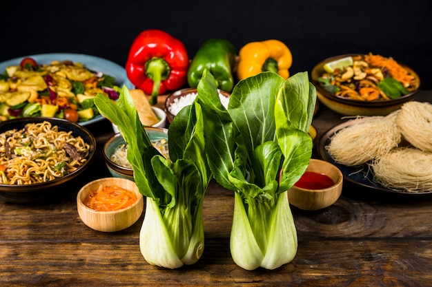 Two bokchoy in front of the thai delicious food on desk