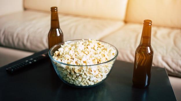 黒いテーブルのボウルにビールとポップコーンの2本。テレビを見るのを待っています