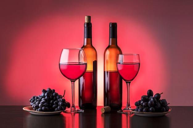Две бутылки вина, рюмка и виноград. различные сорта красного вина.