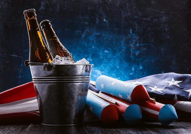 Two bottles of beer in an ice bucket with the american flag lying nearby and rockets for fireworks. independence day celebration concept