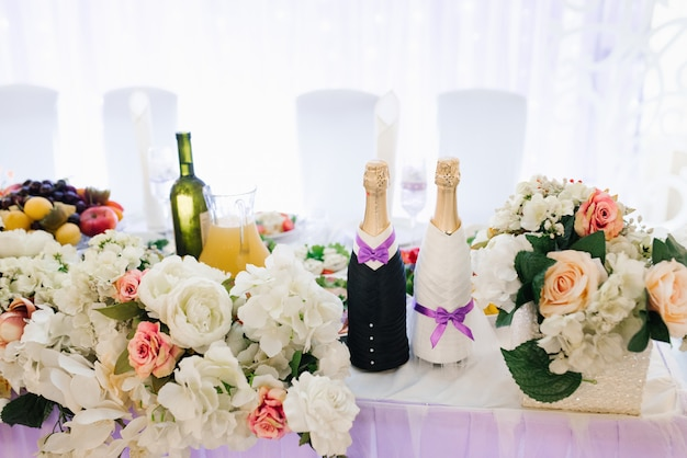 Two bottles of champagne, dressed as the bride and groom, stood on the wedding party table in flowers
