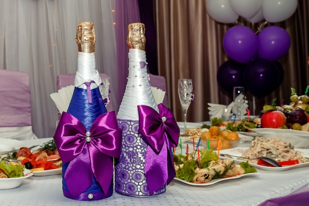 Two bottles of champagne in violet decor on a banquette table