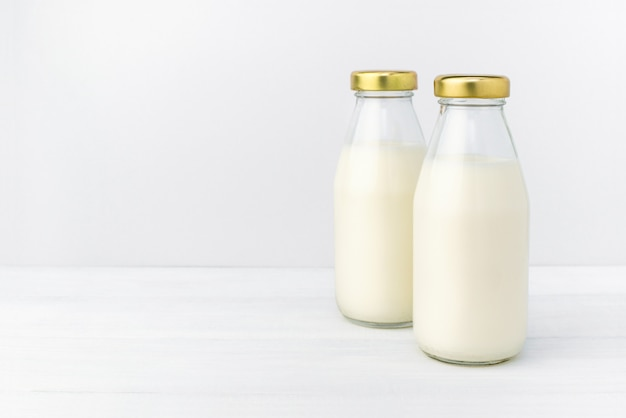 Two bottles of a fresh milk in a bottle with golden cap, oatmeal, almond, alternative natural drink.