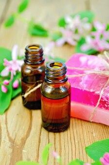 Две бутылки ароматического масла, розовое домашнее мыло
