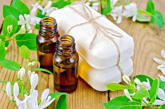 アロマオイル2本、白い石鹸2本、葉のある枝、木の板の背景にスイカズラの白い花