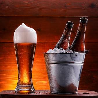 얼음 양동이와 무성한 거품과 맥주 한 잔에 맥주 두 병