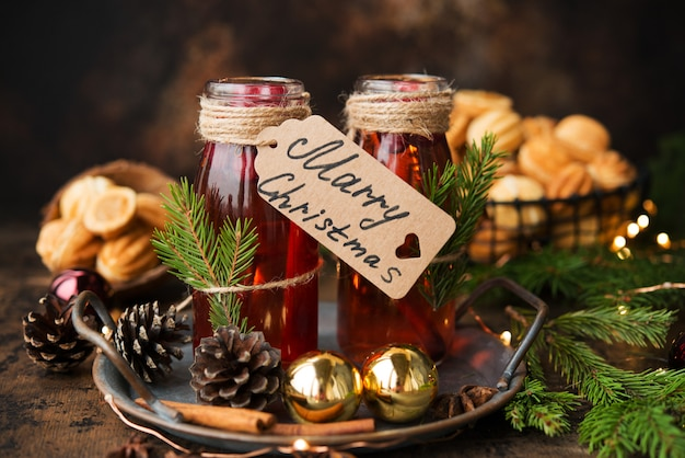 ホットクリスマスの2つのボトルは、木製の壁にスパイスとホットワイン。