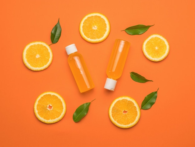 Две бутылки апельсинового сока и апельсинов с листьями на оранжевом фоне. плоская планировка.