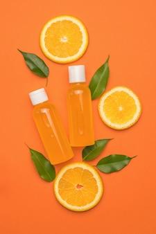 Две бутылки апельсинового сока, листья и кусочки апельсина на оранжевом фоне. плоская планировка.