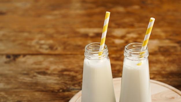 黄色い紙ストローと木製のテーブルに有機素朴なミルクの2本。コピースペース