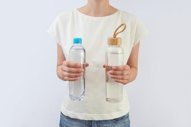 ライトグレーのテーブルに対して女性の手にきれいな天然水が入ったプラスチックとガラスのボトル2本、コピースペース。ゼロウェイストのコンセプト。使い捨てプラスチックの代わりに再利用可能なガラス瓶を使用します。
