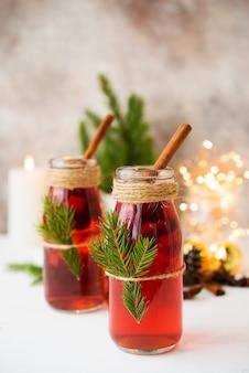 クリスマスの花輪とクリスマスの装飾の白いテーブルにベリーとスパイスの伝統的なお祝いグリューワイン2本