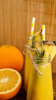 종이 빨대가 있는 열대 주스 두 병. 장식용 오렌지, 파인애플, 로즈마리. 나무 배경입니다. 세로 사진