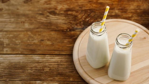 Two bottles of organic rustic milk on wooden table with yellow paper straws. copy space