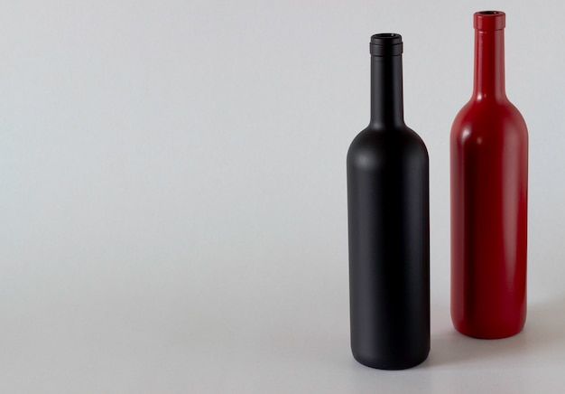 Two bottles of wine of black and red on a white background.