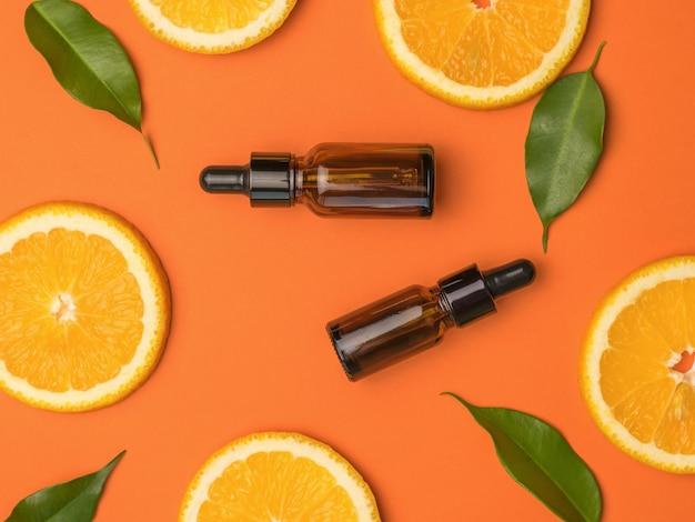 스포이드가 있는 두 병, 오렌지 조각, 오렌지 배경에 나뭇잎. 자연 요법 치료의 개념입니다.