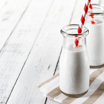 赤い縞模様のストローとライト木製のミルクと2本のボトル