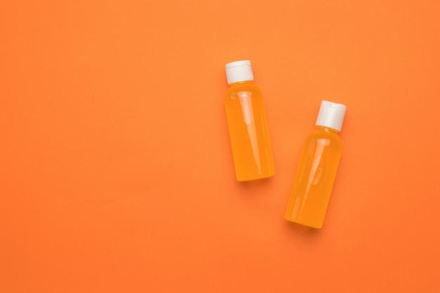 Two bottles with an orange drink on an orange background. minimalism.