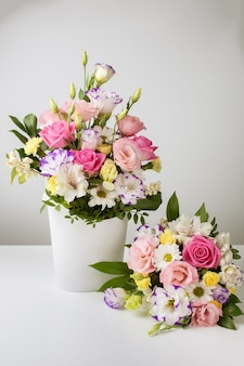 Two bouquets of different sizes in a white paper box