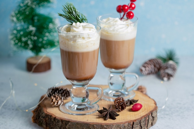 Two bowl ice cream on wooden board with christmas decorations.