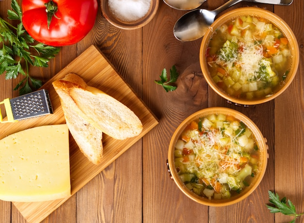 Two bowl of minestrone soup with cheese on cutting board and vegetables