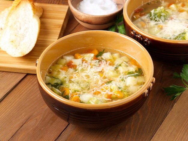 Two bowl of minestrone soup with toast on rustic wooden background, side view.