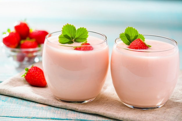 Two bowl of strawberry yogurt on wooden background