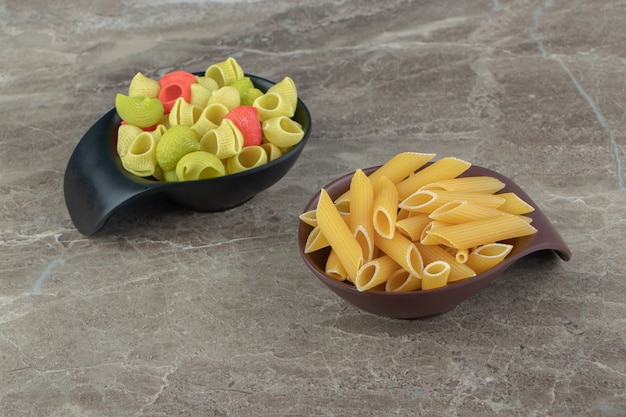 Two bowls of colorful seashell and penne pasta on marble surface