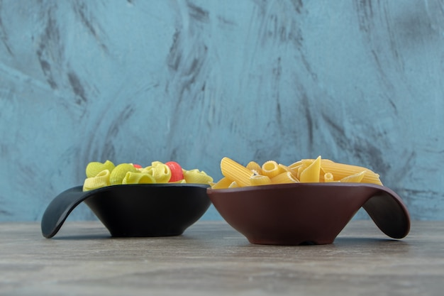 Two bowls of colorful seashell and penne pasta on marble surface.