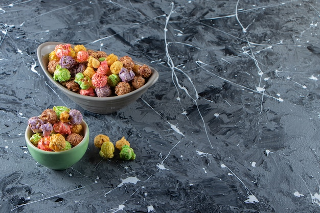 Two bowls of colorful tasty popcorns on marble surface.