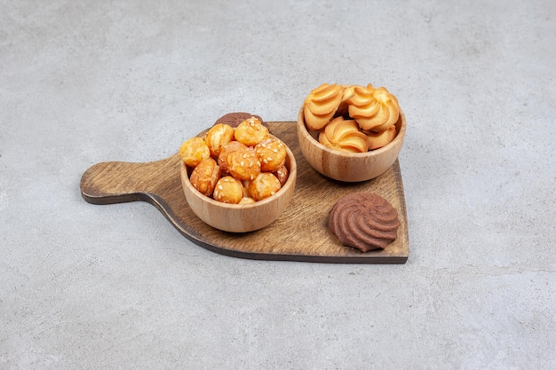 Two bowls of cookies next to brown cookies on wooden board on marble surface.