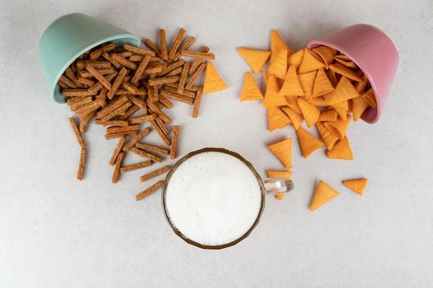 Due ciotole di cracker e un bicchiere di birra