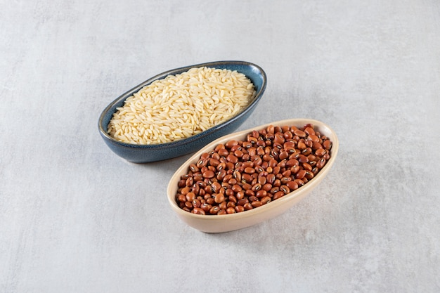 Two bowls full of raw rice and beans on stone background.