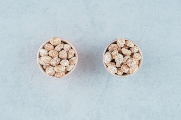 Due ciotole piene di pan di zenzero dolce e delizioso su superficie bianca