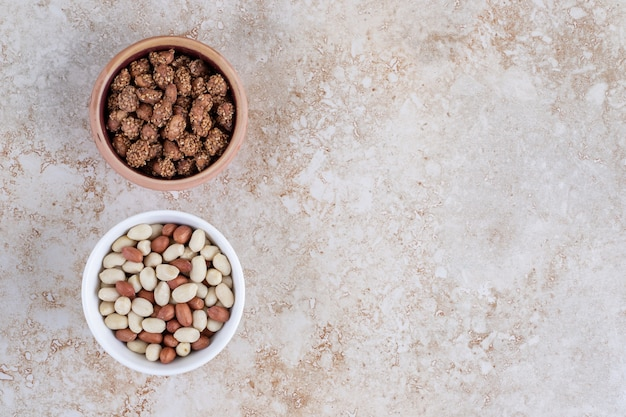 Two bowls of healthy peeled peanuts placed on a stone background .