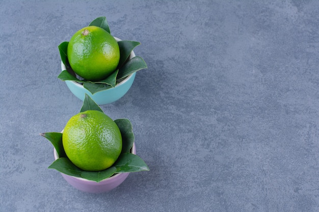 Two bowls of lemons, on the dark surface