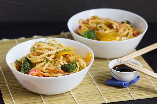 Two bowls of noodles with vegetables and soy sauce on a bamboo mat