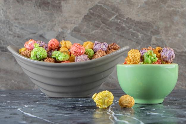 대리석 표면에 화려한 맛있는 팝콘 두 그릇.