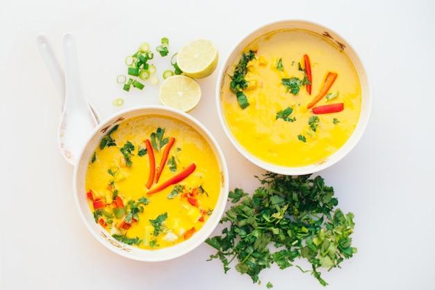 カットグリーンパセリ、ライムのスライス、スプーン、白い背景で隔離の新鮮なココナッツカレースープの2つのボウル。夕食のカレーボウル。ベジタリアン料理のコンセプト