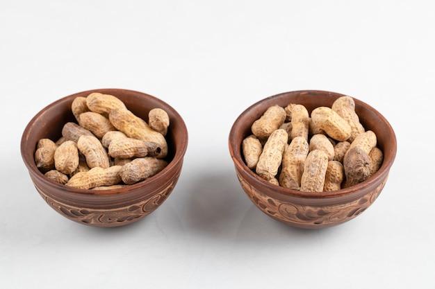 白い表面に隔離された殻の新鮮なピーナッツの2つのボウル。