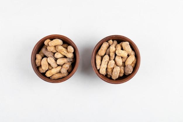 白い表面で隔離された殻の新鮮なピーナッツの2つのボウル