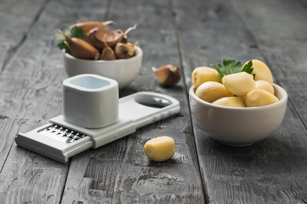 木製のテーブルにニンニク2杯とおろし金。キッチンに人気のスパイス。