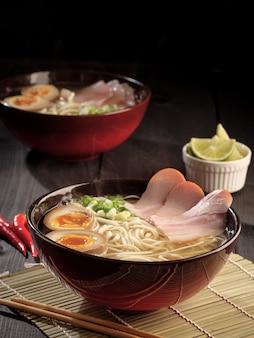 뜨거운 돼지 고기라면 두 그릇과 찐 계란 절임. 세로 사진.