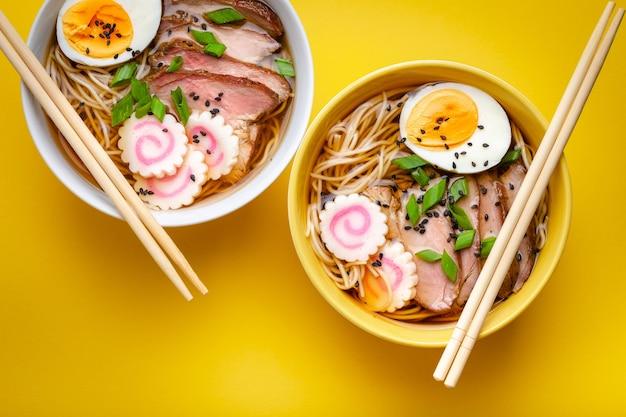 고기 국물, 얇게 썬 돼지고기, 나루토마키, 파스텔 노란색 배경에 노른자가 든 계란을 곁들인 일본 국수 라면 두 그릇. 일본의 전통 요리, 평면도, 클로즈업, 개념