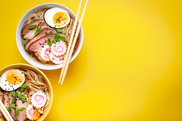 고기 국물, 얇게 썬 돼지고기, 나루토마키, 파스텔 노란색 배경에 노른자가 든 계란을 곁들인 일본 국수 라면 두 그릇. 일본의 전통 요리, 위쪽 전망, 클로즈업, 텍스트 공간