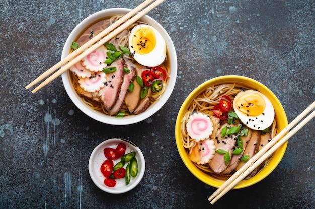 일본 국수 라면 두 그릇, 고기 국물, 얇게 썬 돼지고기, 나루토마키, 소박한 돌 배경에 노른자가 있는 계란. 일본의 전통 요리, 평면도, 클로즈업, 개념