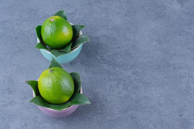 Две миски лимонов на темной поверхности