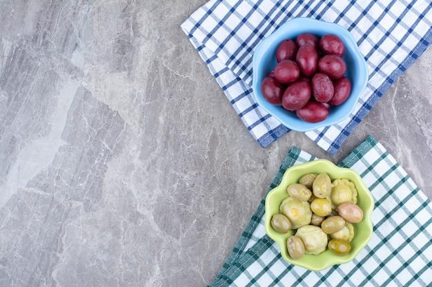 Две миски маринованных овощей и слив со скатертями.